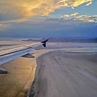 A jetliner comes in for a landing at Salt Lake City International Airport, with a sunset illuminating Great Salt Lake & Antelope Island in the background.