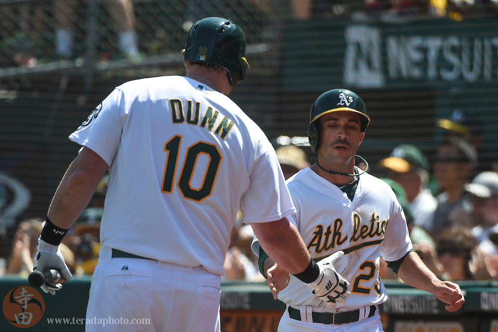 September 6, 2014; Oakland, CA, USA; Oakland Athletics left fielder Sam Fuld (23, right) is congratulated by designated hitter Adam Dunn (10) after scoring on a sacrifice fly by first baseman Brandon Moss (37, not pictured) against the Houston Astros during the third inning at O.co Coliseum.