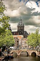 """La vieille eglise (Oude Kerk en neerlandais) est la plus ancienne eglise d'Amsterdam (d'ou son nom): les premiers travaux datent de l'an 1300.<br /> Situee aujourd'hui sur l'Oudekerksplein, elle fut construite sur les vestiges d'une chapelle en bois edifiee par les pecheurs qui la dedierent a Saint Nicolas, leur patron. <br /> Remaniee au xviesiècle, elle melange les styles gothique et Renaissance. En 1578, elle fut convertie au culte reforme.<br /> <br /> The 800-year-old Oude Kerk (""""old church"""") is Amsterdam's oldest building and oldest parish church, founded ca. 1213 and consecrated in 1306 by the bishop of Utrecht with Saint Nicolas as its patron saint. After the Reformation in 1578 it became a Calvinist church, which it remains today. It stands in De Wallen, now Amsterdam's main red-light district. The square surrounding the church is the Oudekerksplein."""