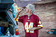 SHOT 10/16/16 6:12:12 PM - Paul Hobson of Steamboat Springs, Co. takes a swig of rum while camping at the Airport camp spot on the White Rim. The White Rim is a  mountain biking trip in Canyonlands National Park just outside of Moab, Utah. The White Rim Road is a 71.2-mile-long unpaved four-wheel drive road that traverses the top of the White Rim Sandstone formation below the Island in the Sky mesa of Canyonlands National Park in southern Utah in the United States. The road was constructed in the 1950s by the Atomic Energy Commission to provide access for individual prospectors intent on mining uranium deposits for use in nuclear weapons production during the Cold War. Four-wheel drive vehicles and mountain bikes are the most common modes of transport though horseback riding and hiking are also permitted.<br /> (Photo by Marc Piscotty / © 2016)