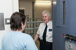 Prison officer talking to a prisoner in her cell, HMP Bronzefield, women's prison in Surrey