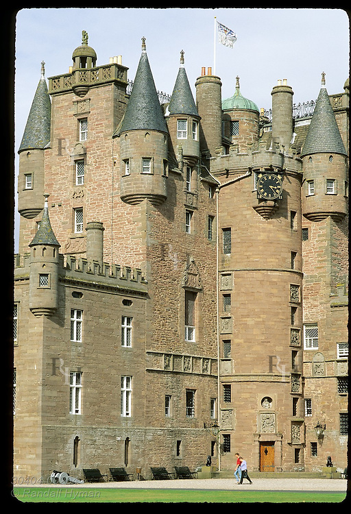 Couple walks past clock tower at front of Glamis Castle, girlhood home of Queen Mother and setting for Macbeth; Glamis, Scotland.