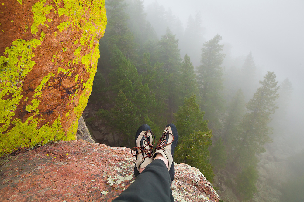 Ethan Welty relaxes on a rock ledge while climbing the First Flatiron (Direct East Face, 5.6) to admire the colorful lichen and pine trees shrouded in fog below.
