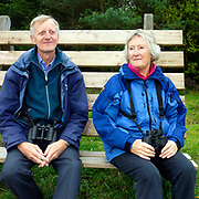 A pair of birdwatchers sit on a bench holding binoculars, North York Moors National Park, North Yorkshire, UK