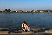 Twee meisjes zitten op een zomerse dag in oktober innig verstrengeld aan de Waalkade in Nijmegen.<br /> <br /> Two girls are hugging each other at the Waalkade in Nijmegen on a sunny day in October.