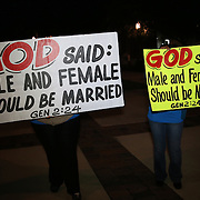 Protesters hold up signs outdoors as couples receive same sex marriage licenses at the Osceola County Courthouse in Kissimmee, Florida on Tuesday, January 6, 2014.  (AP Photo/Alex Menendez)