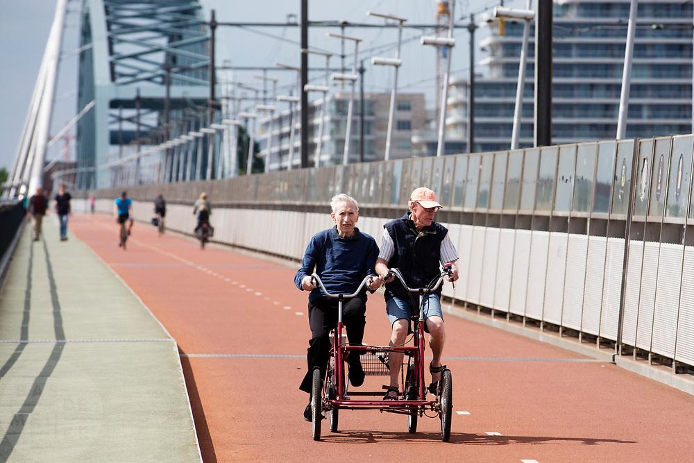 In Nijmegen rijden fietsers op een speciale tandem waar ze naast elkaar zitten over de Snelbinder, de fietsbrug tussen Nijmegen en Lent.<br /> <br /> In Nijmegen cyclists ride at the bridge over the river Waal.