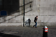 City of London bollard and businessman's shadows on church wall. The man walks along this narrow medieval street called Foster Lane where the 17th century wall of Wren's St Vedast church. Inhaling while walking, he also talks on a smartphone during his private conversation in the heart of the capital's financial centre, founded by the Romans in 43AD.