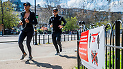 A sign gives instruction on social distancing but is often ignored, partly because ther are too many people out - A sunny day and people are out in reasonable numbers, throughout London, to get their daily exercise.  The 'lockdown' continues for the Coronavirus (Covid 19) outbreak in London.