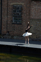 © Licensed to London News Pictures.<br /> 12/07/2020. London, UK. Amelia Townsend performs by Regent's Canal. A group DistDancing showcasing ballet and contemporary dance at Hoxton Docks, north London. The group was created during the lockdown as a platform for open air live performances; an initiative started by Royal Ballet dancers Chisato Katsura and Valentino Zucchetti in collaboration with Hoxton Docks. Photo credit: Marcin Nowak/LNP
