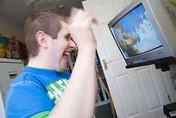 Teenage boy with Autism having fun watching television,