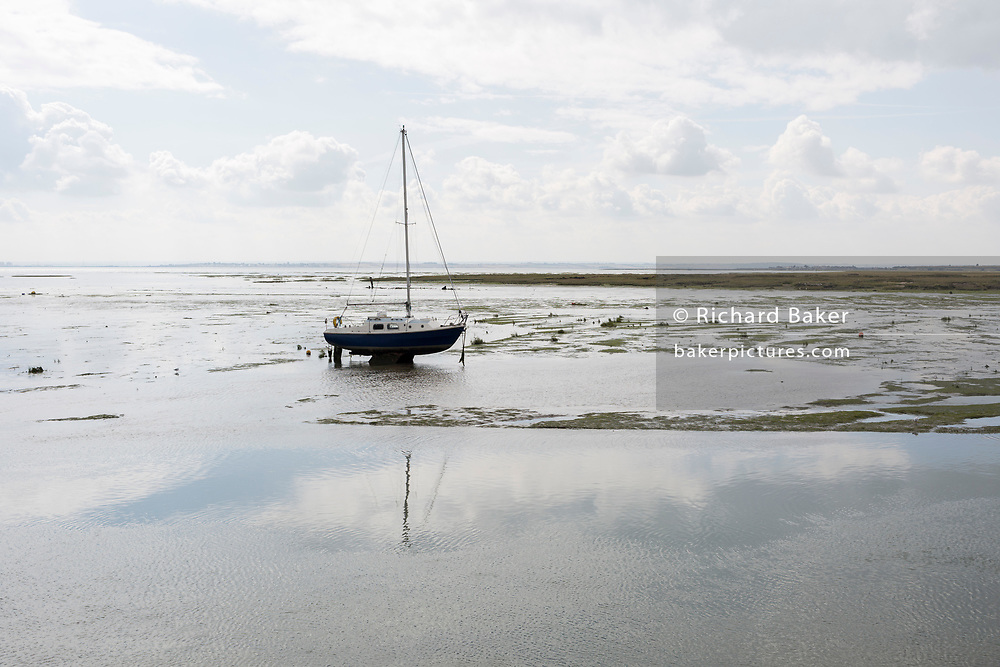 A landscape of a single yacht sitting upright in low-tide estuary mud at Old Leigh, on 10th September 2019, in Leigh-on-Sea, Essex, England.