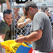 NASCAR Sprint Cup driver Juan Pablo Montoya (42) is seen signing a Columbian flag, in the garage area during the NASCAR Coke Zero 400 Sprint practice session at the Daytona International Speedway on Thursday, July 4, 2013 in Daytona Beach, Florida.  (AP Photo/Alex Menendez)