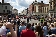 A crowd of tourists and local residents watches the 1st Battalion Grenadier Guards, led by the Grenadier Guards Corps of Drums, on their approach to Windsor Castle to perform the Changing of the Guard ceremony on 29th July 2021 in Windsor, United Kingdom. The ceremony, which is also known as Guard Mounting, was reinstated on 22nd July for the first time since the beginning of the Covid-19 pandemic in March 2020.