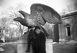 Snapshot of a father and son beside a statue of an eagle at the Bronx Zoo.