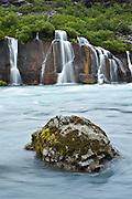 Beautiful waterfall falling through the old lava in Hraunfossar.