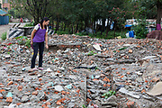 A Nepalese woman searches through rubble remains of the centre she used to work at in United Nations Park, Paurakhi Basti, next to the Bagmati River in the centre of Kathmandu, Nepal.  This used to be a slum area housing many Nepalese people. The government forces arrived in the middle of the night and used tear gas to displace the residents before demolishing their homes.