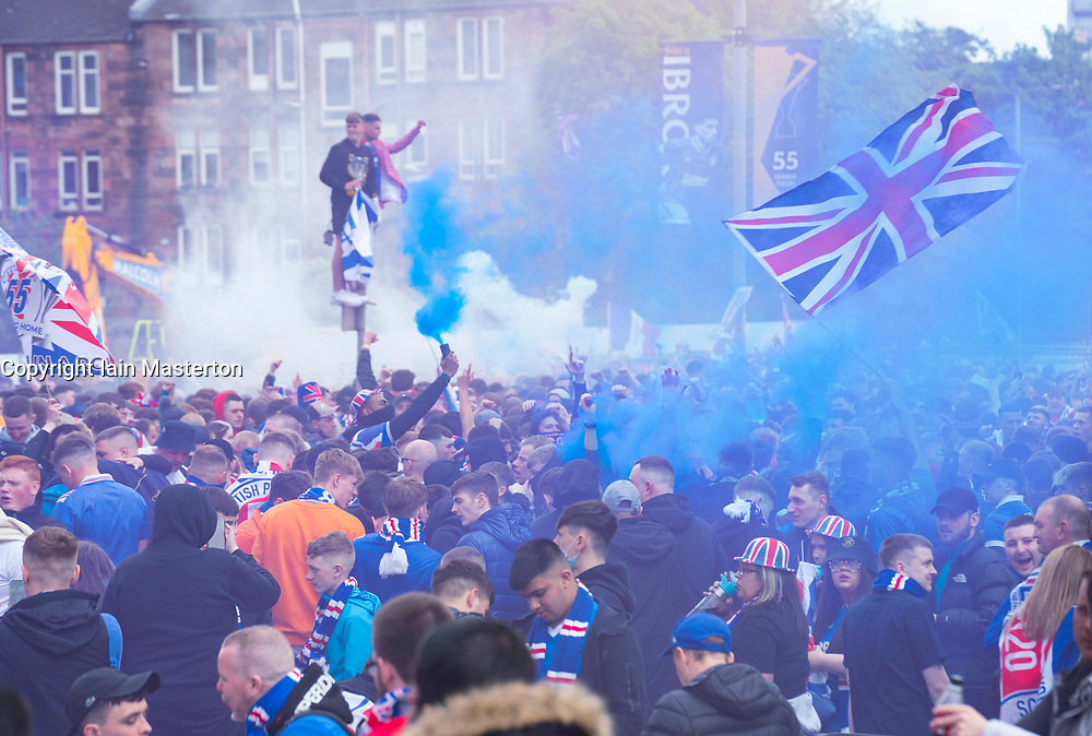 Glasgow, Scotland, UK. 15 May 2021. Thousands of supporters and fans of Rangers football club descend on Ibrox Park in Glasgow to celebrate winning the Scottish Premiership championship for the 55th time and the first time for 10 years. Smoke bombs and fireworks are being let off by fans tightly controlled by police away from the stadium entrances. Pic; Fans celebrate after full time at the gates of Ibriox. Iain Masterton/Alamy Live News