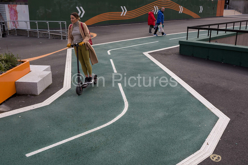 A motorised scooter lady takes the shortest route through the bends of a new cycling path, a regenerated landscape created outside Croydon College and Fairfield Hall, on 20th January 2020, in Croydon, London, England.