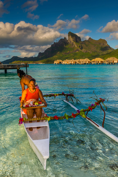 Polynesian couple in an outrigger canoe in the lagoon, Four Seasons Resort Bora Bora, French Polynesia.