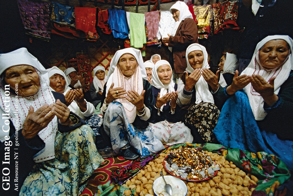 In the village of Akesai, elderly Khazak women turn their palms up in prayer at a gathering marking the first anniversary of the death of a tribal leader. The seven thousand Khazaks in the village are the descendants of nomads whom the Chinese border walls were meant to shut out. Gansu, China