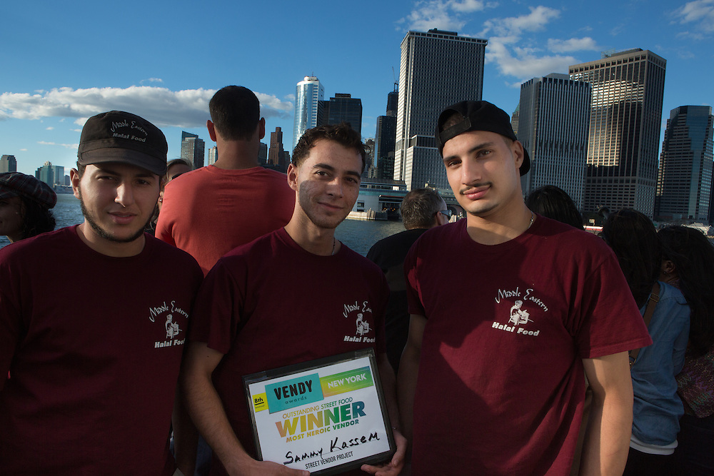 Employees of Sammy Kassem's Middle Eastern Halal Foods pose on the ferry back to Manhattan with the Most Heroic Vendor award. The awards are sponsored by the Street Vendor Project of the Urban Justice Center.