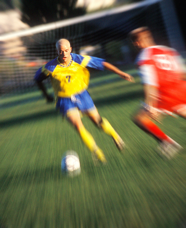 Two young men playing soccer.  Blur / zoom effect. Grainy film.<br />