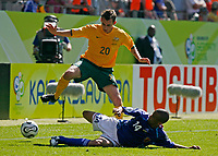 Photo: Glyn Thomas.<br />Australia v Japan. Group F, FIFA World Cup 2006. 12/06/2006.<br />Japan's Alessandro Santos (R) slides in to tackle Australia's Luke Wilkshire.