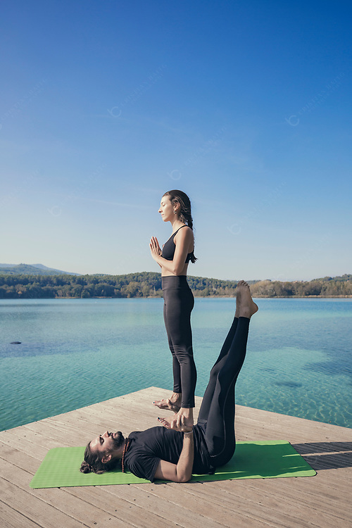 Couple practicing acroyoga in nature at beautiful lake Acroyoga foot to hand pose