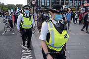 Police wearing face masks at the Marine Rebellion march on 6th September 2020 in London, United Kingdom. Ocean Rebellion, Sea Life Extinction, Animal Rebellion and Extinction Rebellion joined together to celebrate the biodiversity found in our seas, and to grieve at the destruction of the Earth's oceans and marine life due to climate breakdown and human interference, and the loss of lives, homes and livelihoods from rising sea levels. Extinction Rebellion is a climate change group started in 2018 and has gained a huge following of people committed to peaceful protests. These protests are highlighting that the government is not doing enough to avoid catastrophic climate change and to demand the government take radical action to save the planet.