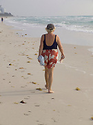elderly woman walking on the beach by her self Miami