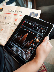 Woman using iPad tablet computer to check stock market prices