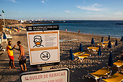 A sign shows rules for wearing facemasks on the beach at Playa Dorada in Lanzarote, Spain on 22nd November 2020. Beaches and resorts across the island are nearly deserted since tourism plummeted due to Covid restrictions elsewhere in Europe. Although the Canary Islands have been relatively unscathed by the virus, with 155 lives lost from 2.1 million residents, the region is heavily dependent on tourism and locals are hoping that numbers recover as lockdown measures ease and vaccines potentially reduce the numbers of infections.