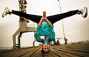 Young female breakdancing in a handstand pose with the head on floor
