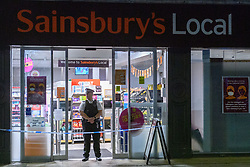 © Licensed to London News Pictures. 26/08/2021. London, UK. A police officer maintains a scene watch at a Sainsbury's Local store on Fulham Palace Road following the arrest of a man on suspicion of contamination of goods with intention of causing public harm or anxiety after foodstuffs at supermarkets were injected with needles. Metropolitan Police were called at approximately 19:40BST on Wednesday 25/08/2021 after a man was reported to be shouting abuse at people in the street. The man is reported to have gone into three supermarkets in Fulham Palace Road and injected foodstuffs with a number of needles. Photo credit: Peter Manning/LNP