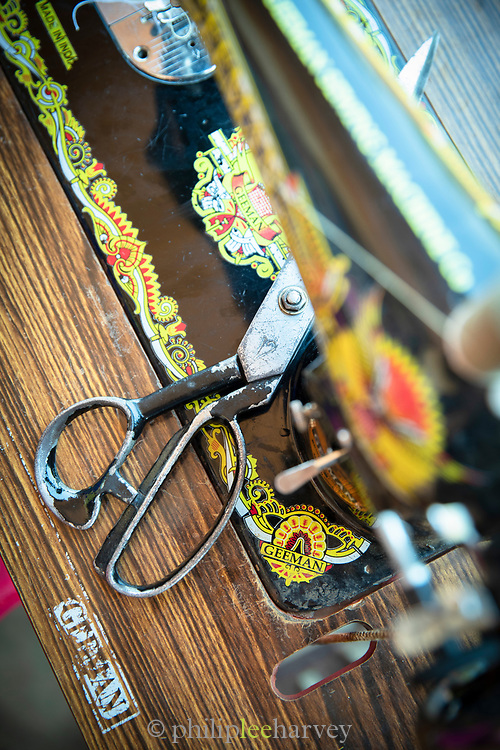 Close-up of sewing machine and scissors at Design and Tailoring Centre, Musoto, Uganda