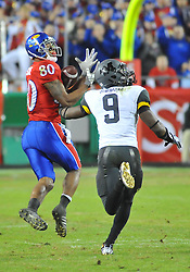 Nov 28, 2009; Kansas City, MO, USA; Kansas wide receiver Dezmon Briscoe (80) makes the catch as Missouri safety Jasper Simmons (9) attempts coverage in the fourth quarter at Arrowhead Stadium. The Tigers won 41-39.Mandatory Credit: Denny Medley-US PRESSWIRE