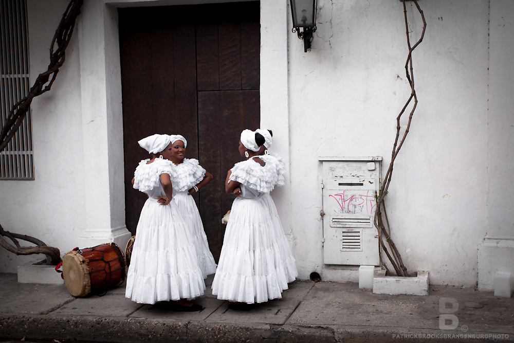 A behind the scenes look at a group of four African American women in beautiful traditional white dresses against a white background in downtown Cartagena, Colombia.