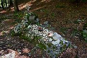 The grave to an unknown Russian Prisoner of war at the wooden church (Ruska Capela) built by Russian Prisoners of War during WW1, in honour of their comrades who died building the Vrsic Pass road (Ruska Cesta) near kranjska Gora, on 22nd June 2018, in Triglav National Park, Julian Alps, Slovenia.