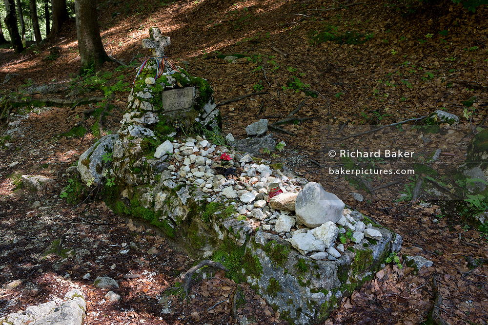 The grave to an unknown Russian Prisoner of war at the wooden church (Ruska Capela) built by Russian Prisoners of War during WW1, in honour of their comrades who died building the Vrsic Pass road (Ruska Cesta) near kranjska Gora, on 22nd June 2018, in Triglav National Park, Julian Alps, Slovenia.