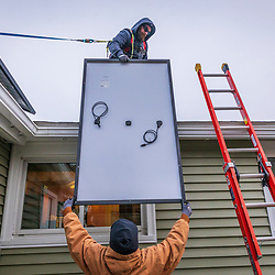 Revision Energy employees installing solar panels on a single family home in Lowell, Massachuetts.