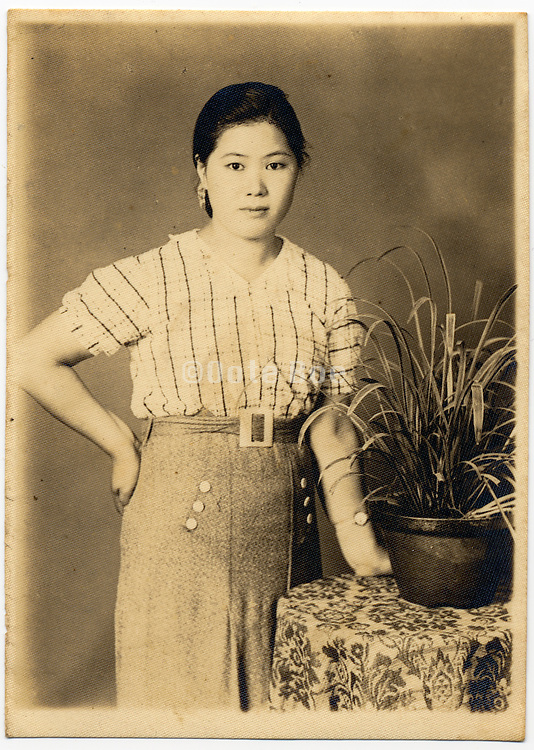 Studio portrait of Asian woman in western style clothing.