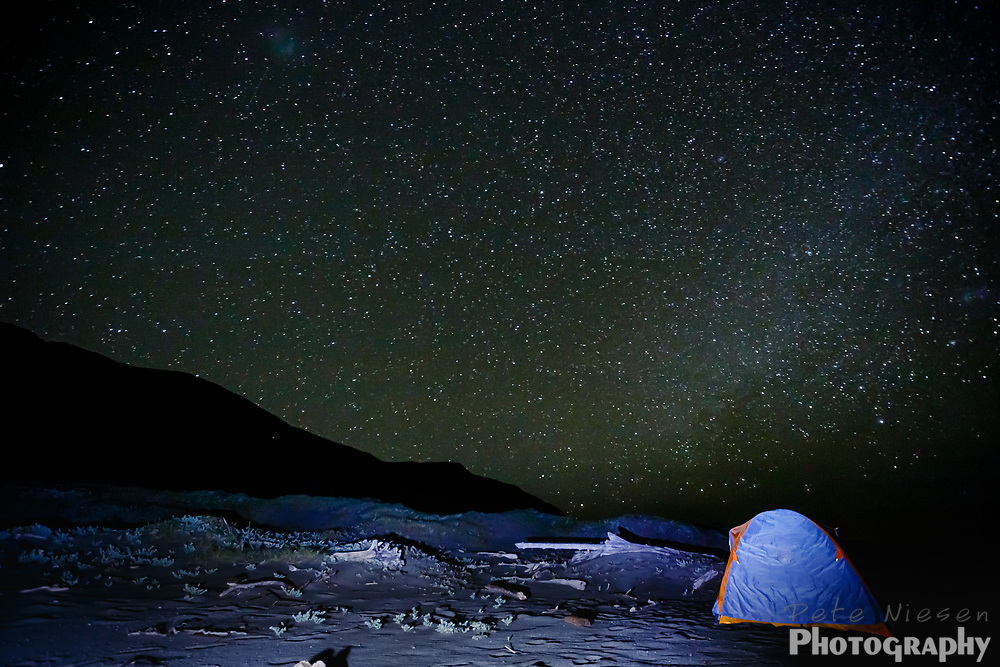 Nighttime view of stars and tent on beachside campsite