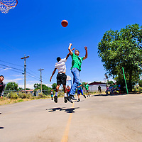 Blake Haubner, 14 of Decatur, IL makes a jump shot as he is defended by Elijah Soce, 15 of Gallup, during a pickup basketball game on Tuesday at Gamerco Church of God basketball court in Gamerco. Haubner is on a mission trip with South Shores Christian Church.