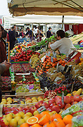 A market stall on the sunday market on the Quai des Chartrons with lots of colourful fruit and vegetables: oranges, apples, strawberries, radishes, plums. Several other market stands in the background. , Bordeaux, Aquitaine, France
