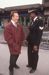 Community police officer standing in street talking to man,