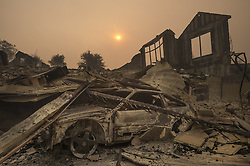 October 10, 2017 - Santa Rosa, California, U.S. - The sun rises through a cloud of smoke over a burned home and destroyed car, in the Rincon Ridge area after a wildfire in Sonoma County in Santa Rosa, Calif. (Credit Image: © Paul Kitagaki Jr/Sacramento Bee via ZUMA Wire)