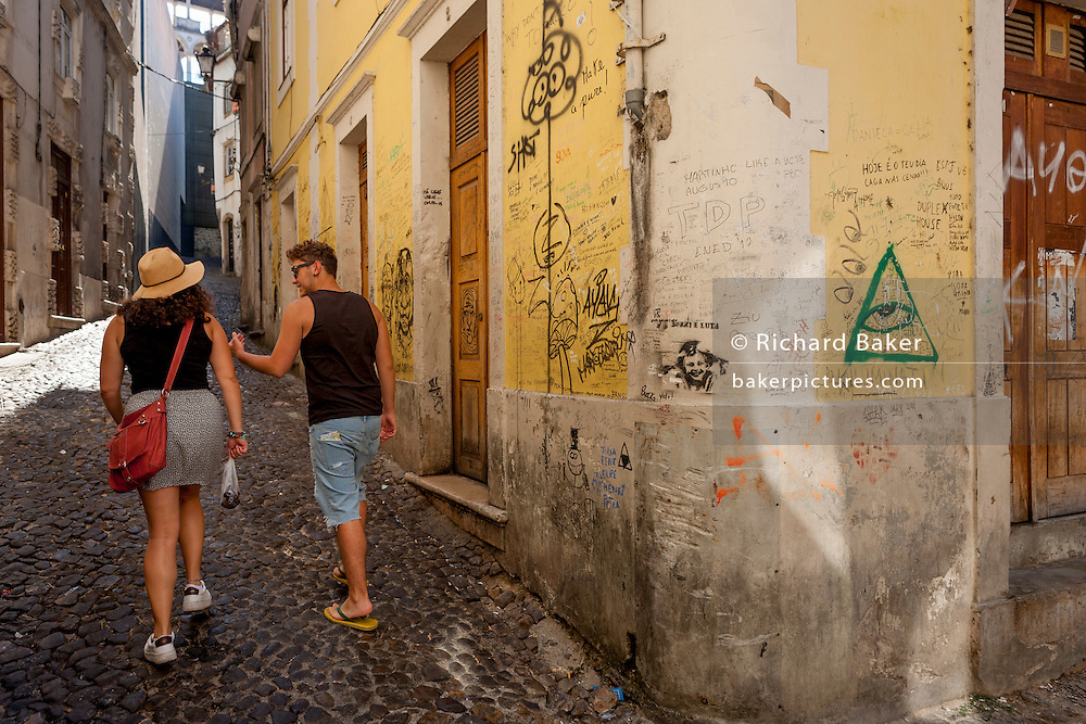 Students walk past scrawled messages on a street corner wal near Coimbra University, on 17th July, at Coimbra, Portugal. (Photo by Richard Baker / In Pictures via Getty Images)