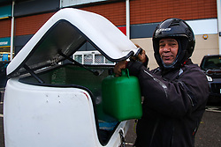 © Licensed to London News Pictures. 01/10/2021. London, UK. A fast food delivery driver holds a fuel can full of petrol on the eighth day at Sainsbury's petrol station in north London as the fuel crisis enters its second week. There are continuing fears of fuel running out due to a shortage of HGV drivers. Photo credit: Dinendra Haria/LNP
