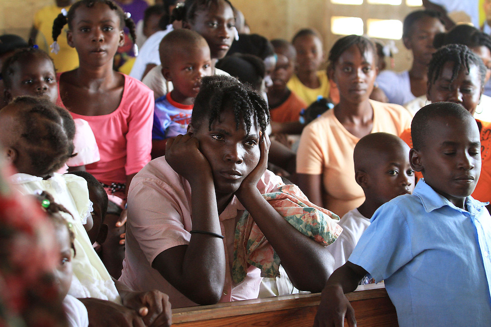 Mothers and their children listen to a lecture regarding childhood health during a 'Celebration of Life' ceremony in Welsh, Haiti.